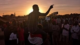 Sudanese protesters rally in front of the military headquarters in the capital Khartoum at sunset, 15 April 2019.