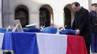 French President Francois Hollande puts on a coffin the Legion d'Honneur medal, the Legion of Honour, France's highest award, during a tribute ceremony dedicated to the nine French Air Force personnel in the Invalides courtyard in Paris February 3, 2015.