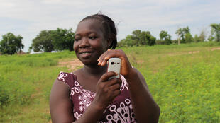 Mariama Keita of Sikilo Village checks an SMS message advising on current weather and farming conditions.