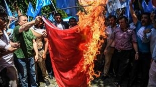 Uighur activists and Turkish nationalists burn a Chinese flag during a protest in Istanbul this year