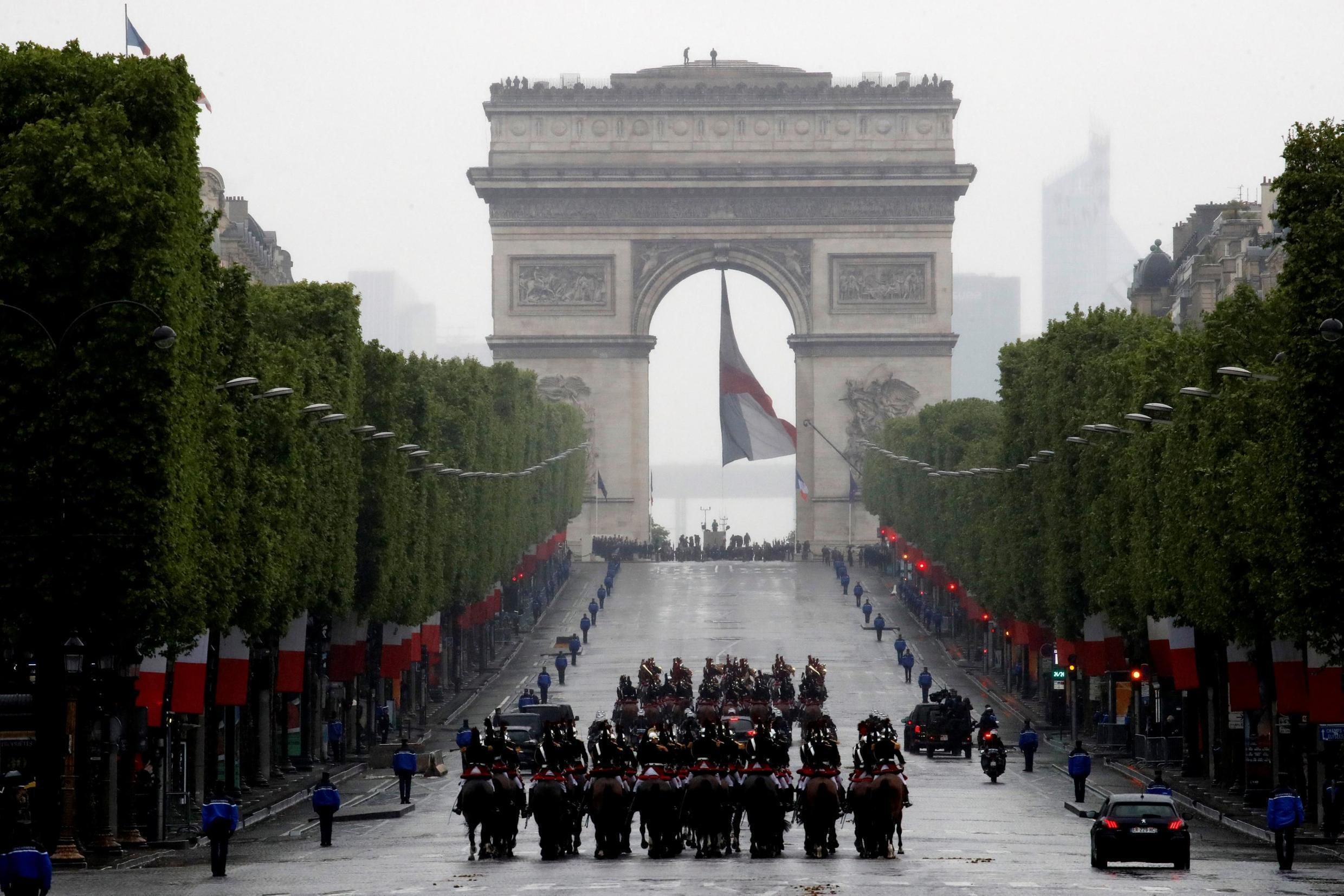 French President Emmanuel Macron's convoy drives up the Champs-Elysées to mark Victory Day at the Arc de Triomphe in Paris.