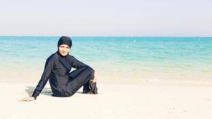 Propaganda de burquíni mostra mulher coberta em praia.