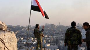 Um soldado do exército sírio ao lado da bandeira nacional no leste de Alepo.