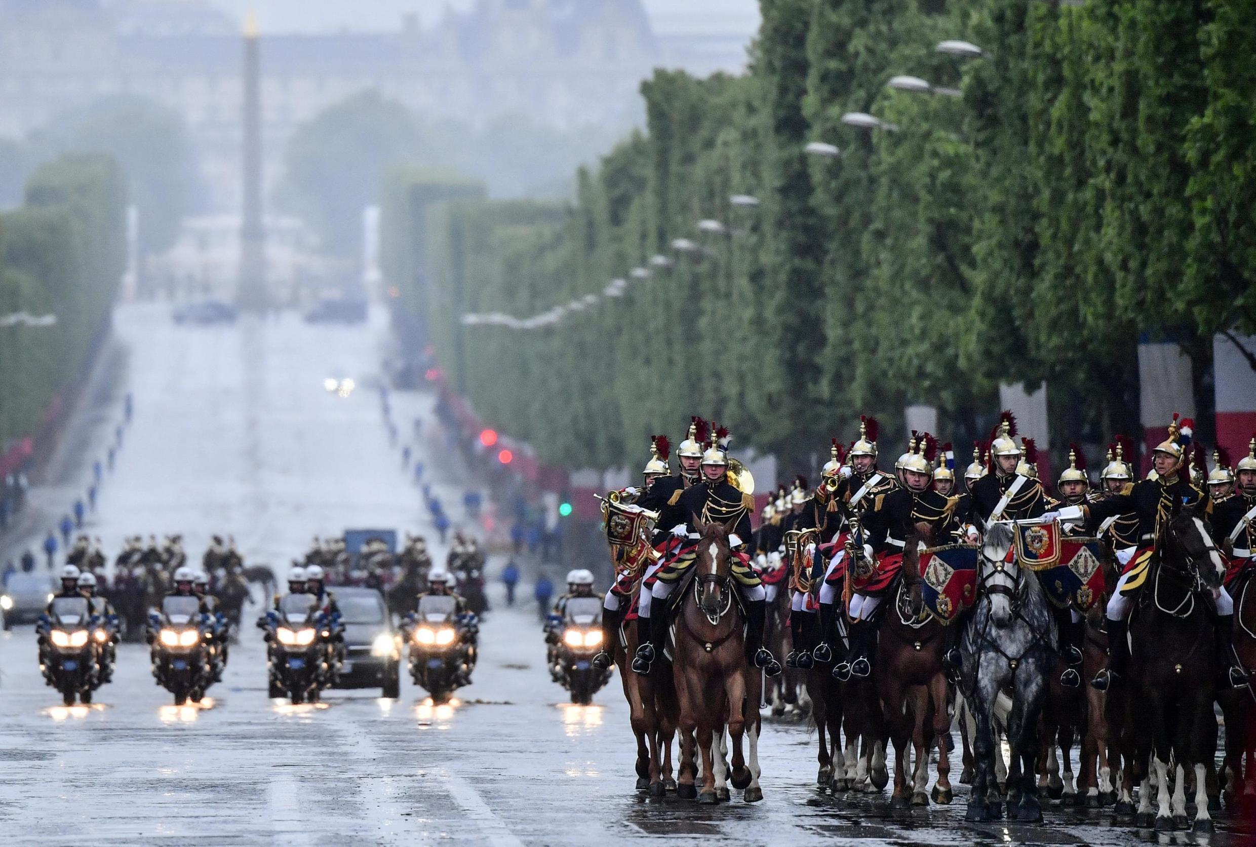 Republican guards ride down the Champs-Elysées in front of French President's Emmanuel Macron's car arriving for the ceremony marking the end of World War II in Paris.