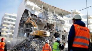 Un bulldozer en action sur un bâtiment détruit par le séisme à Durrës, Albanie, le 2 décembre 2019.