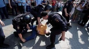 Des forces de l'ordre arrêtent un manifestant qui réclamait des élections locales libres, en face du Parlement régional de Moscou, le 27 juillet 2019.