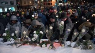 Les gens déposent des fleurs à la mémoire des victimes près du Centre culturel islamique de Québec le 29 janvier 2018.