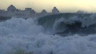 A wave breaks at sunset on the Brittany coast at Penmarch in Finistere