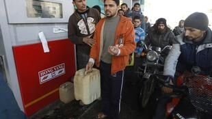 Palestinians wait to fill containers with fuel at a petrol station in Khan Younis in the southern Gaza Strip