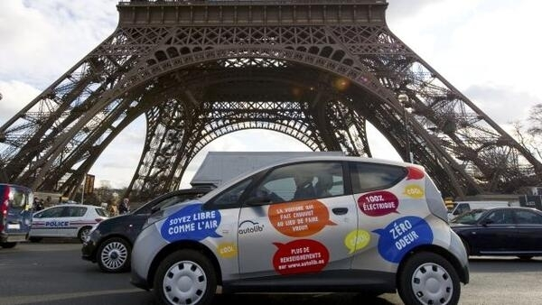 An electric Autolib' car drives by the Eiffel Tower