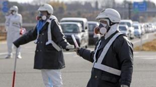 Полицейские в респираторах регулируют  процесс эвакуации людей из окрестностей АЭС в Фукусиме.
