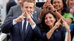 O presidente francês, Emmanuel Macron (esq), e a prefeita de Paris, Anne Hidalgo (direita), e a ministra dos Esportes, Laura Flessel, promovem a candidatura de Paris para os JO de 2024, fazendo o sinal da Torre Eiffel.