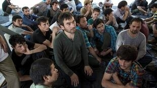 Suspected Uighurs from China's troubled far-western region of Xinjiang sit inside a temporary shelter after they were detained at the immigration regional headquarters near the Thailand-Malaysia border in Hat Yai, Songkla, 14 March 2014.