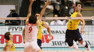 O atacante Giba enfrenta o bloqueio do Irã na partida em que a seleção brasileira venceu por 3 sets a 0.