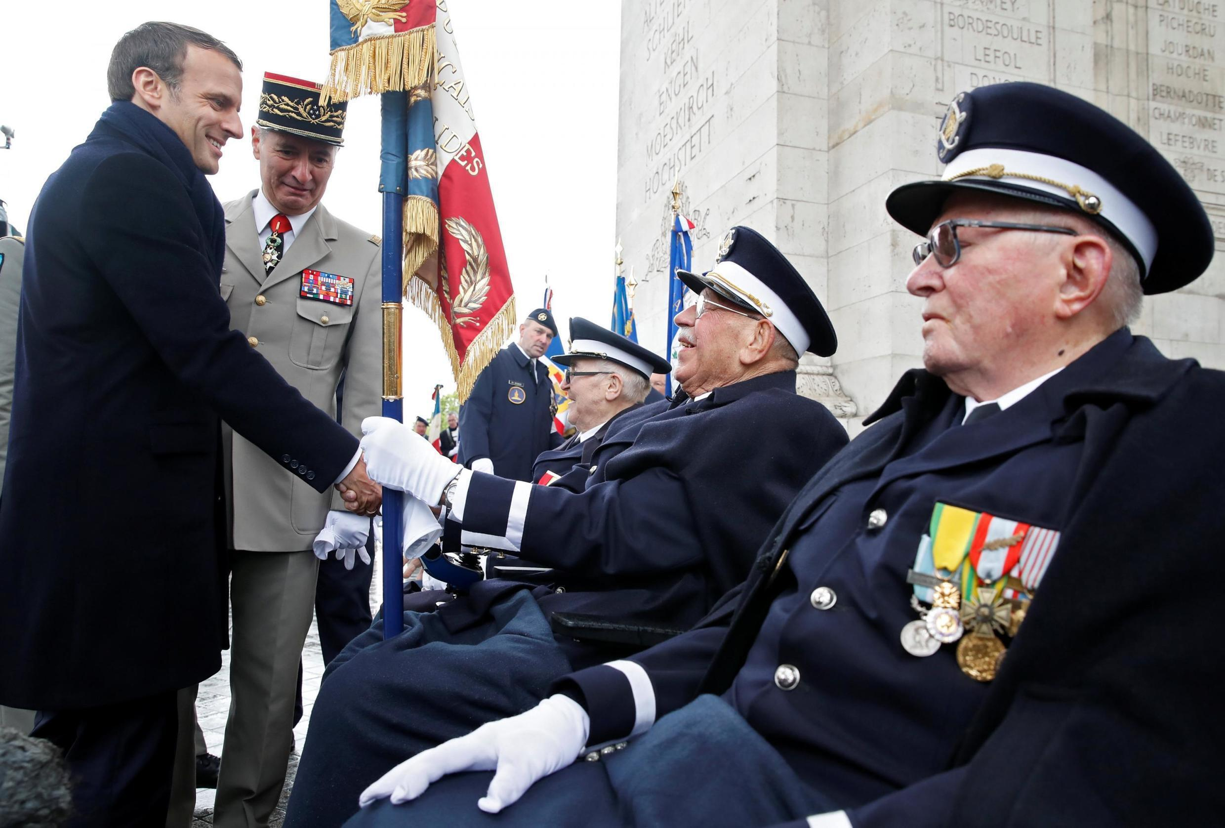 French President Emmanuel Macron greets veterans during a ceremony to mark the end of World War II at the Arc de Triomphe in Paris.