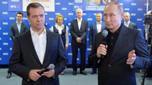 O presidente russo, Vladimir Putin (direita), e o primeiro-ministro Dmitry Medvedev se felicitam pela vitória do partido Rússia Unida nas eleições legislativas.