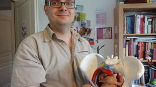 Midwife Nicolas Dutriaux holds a model of a pelvis he uses to explain things to his patients.