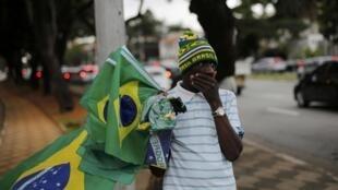 Un vendeur de drapeaux brésiliens dans une rue de Sao Paulo, le 10 juin 2014. La morosité règne sur ce Mondial.