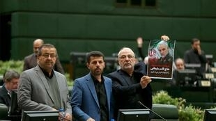 An Iranian lawmaker holding a picture of slain general Qasem Soleimani as he votes during a parliamentary session in Tehran.
