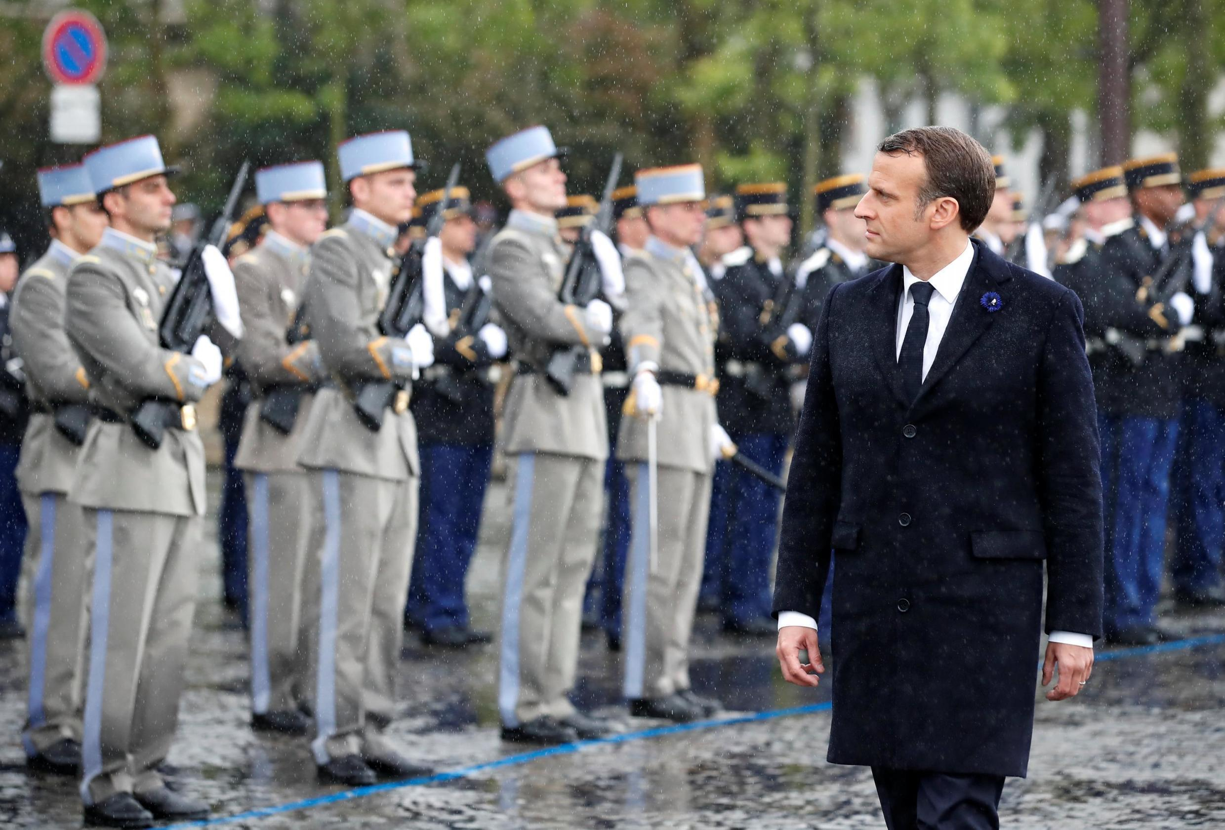 French President Emmanuel Macron reviews troops during a ceremony to mark the end of World War II at the Arc de Triomphe in Paris.