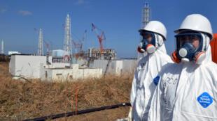 Funcionários em frente à usina nuclear em Fukushima, no norte do Japão