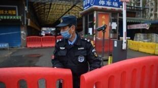 Un officier de police bloquant le marché au poisson de Wuhan, le 24 janvier 2020.