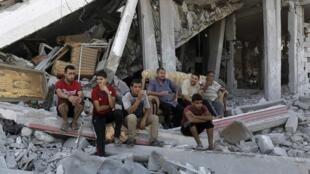 Em segundo dia de trégua, palestinos conversam sentados sobre escombros em Gaza