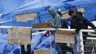 Syrian asylum seekers remove placards from a footbridge after a demonstration at the ferry terminal in Calais, 4 October, 2013