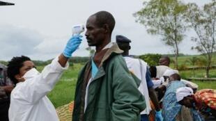 Un soignant teste la température d'un homme lors de son arrivée à Gatumba, à la frontière entre le Burundi et la RDC, le 18 mars 2020.