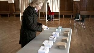 A woman casts her vote at a polling station in Dijon, 20 March 2011.