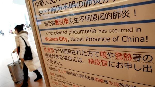 Uma mulher de máscara passa por um aviso de quarentena sobre o surto de coronavírus em Wuhan, China, no saguão de chegada do aeroporto de Haneda em Tóquio, Japão, em 20 de janeiro de 2020.
