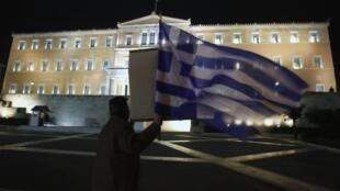 Homem empunha bandeira da Grécia diante do Parlamento do país, em Atenas.