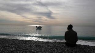 Un migrant sur une plage de galets sur la Côte d'Azur, en France, le 6 février 2020.