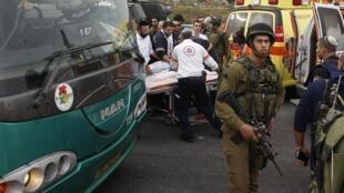 Soldados fazem a segurança para a retirada de uma das vítimas do ataque com ácido perto da colônia de Gush Etzion.