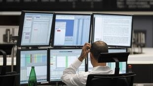 A trader in front of his computers at the Frankfurt stock exchange