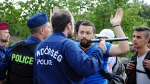 Policiais param um grupo de migrantes perto da cidade de Roszke, na fronteira serbo-húngara, em 9 de setembro de 2015.