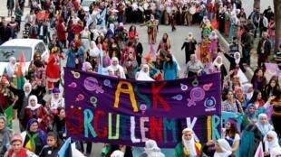 """Na Turquia, mulheres curdas também se manifestaram contra a opressão atrás de uma faixa com o slogan """"amor é ser organizado""""."""