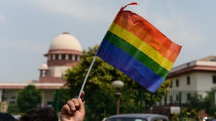 New Dehli, an LGBTI supporter waves a rainbow-symbol flag outside the Supreme Court on 6 September 2018 after the Court scrapped Section 377 to decriminalize adult homosexual relations.