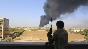 A militia fighter watches smoke rise from a petrol depot at Tripoli airport last month