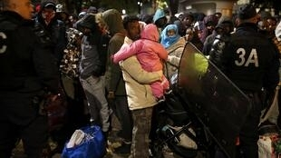 Migrants wait before entering buses as part of their transfer by French authorities to reception centres across the country during the dismantlement of makeshift camps in a street near Stalingrad metro station in Paris, France, November 4, 2016.