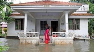 Le changement climatique a un impact dans plusieurs pays. Dans le Kerala, une femme tente d'évacuer l'eau de sa maison inondée, le 11 août 2019.