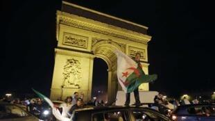 Torcedores argelinos comemoram classificação debaixo do Arco do Triunfo, na Av. Champs Elysées