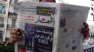 An Algerian man reads En-Nahar newspaper, bearing a picture for the first time of former Algerian intelligence chief General Mohamed Mediene, better known as General Toufik, in Algiers on September 13, 2015