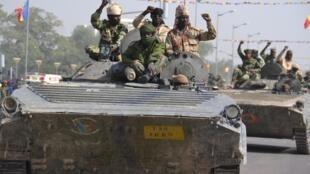 Des soldats tchadiens sur des chars saluant la foule à Ndjamena, le 11 décembre 2015, à leur retour de mission du Niger voisin.