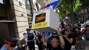 Un homme brandit une urne de vote symbolique, devant le Tribunal de Barcelone, le 19 septembre 2017.