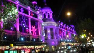 Париж приготовился к встрече праздников: здание магазина «Прентан» мерцает ночью тысячами огней.