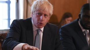 Le Premier ministre britannique Boris Johnson, accompagné du conseiller du Conseil de justice pour la jeunesse, Roy Sefa-Attakora, lors d'une table ronde sur le système de justice pénale au 10 Downing Street à Londres le 12 août 2019.