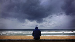 A surfer looks at waves as storm clouds move in from the Pacific Ocean at Sydney's Manly Beach August 26, 2014.