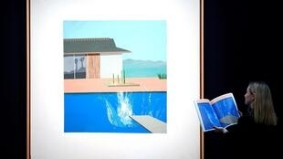 A Sotheby's employee in front of 'The Splash' by David Hockney ahead of the auction in London, 7 February 2020