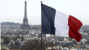 city view shows the French flag above the skyline of the French capital as the Eiffel Tower and roof tops are seen in Paris